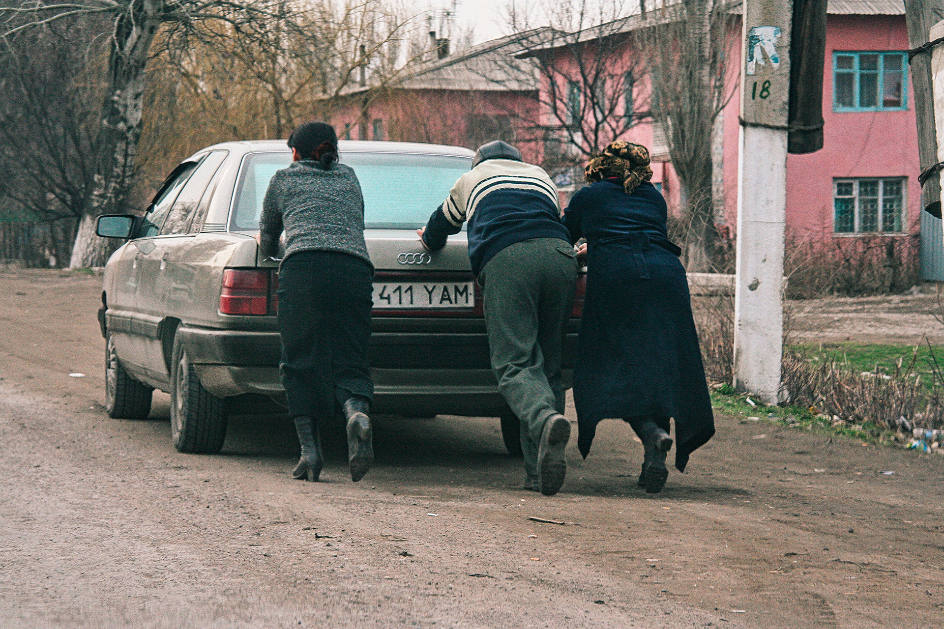 holes, Almaty, bad roads, pushing car, broken car, women, man, problem, genre, Kazakhstan